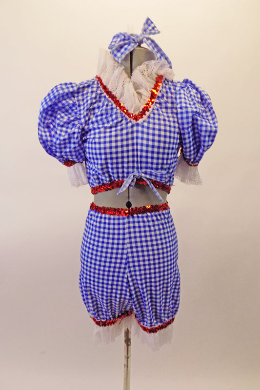 Two-piece blue and white gingham ragdoll themed costume has bloomer style bottom pouffe sleeved half top. There is a wide white lace ruffle at legs, sleeves and neckline with edged with a red sequin accent. Comes with hair bow accessory. Front