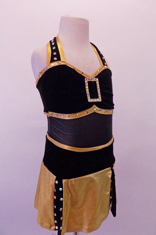 Black & gold dress is two pieces. The halter leotard has black velvet bust area edged with crystal covered gold piping, crystal brooch front accent & black sheer torso. The skirt bottom is a made of gold flaps with crystalled black edging. Comes with a black velvet bowler hat with gold band and crystal brooch accent. Front
