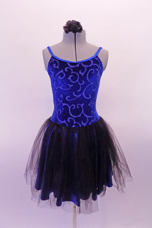 Pretty blue and black camisole dress has a blue velvet scroll pattern in the velvet. The attached blue shiny skirt has and sheer black tulle top layer that creates depth. The back is a lower scoop neck. Comes with a black floral hair accessory. Front