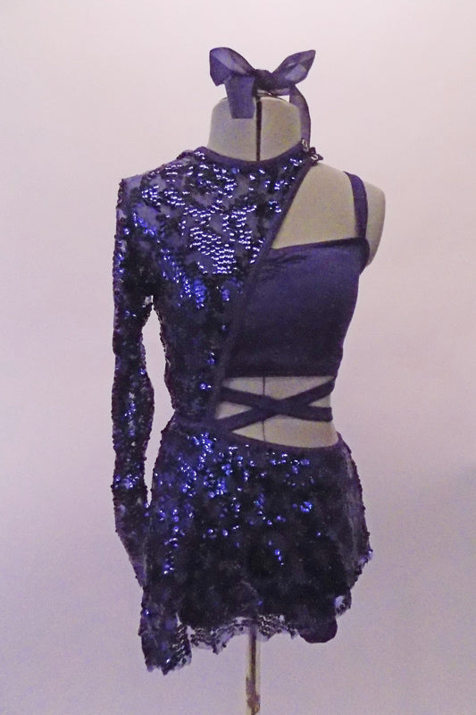 Blue costume is a two-piece joined at the left side of the waist. The base is a half top that gathers at the bust and shorts. The two pieces are attached via a sequined skirt that attaches to both the shorts and the shrug. The shrug is half sided, single sleeved and fully sequined which snaps at the left side. Front
