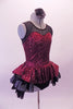 Burgundy sequined leotard dress has black sheer mesh front upper with sweetheart neckline. The sequined peplum sits on top of the open front layered black petticoat skirt, Comes with a black floral hair accessory. Side