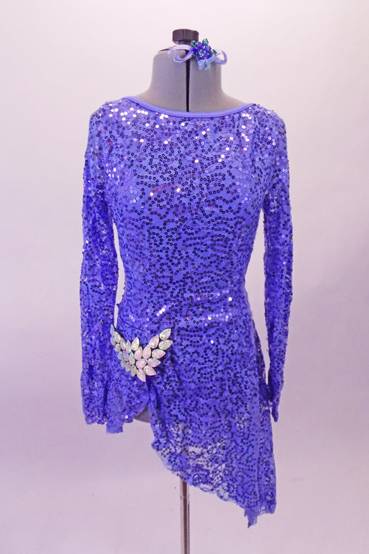Soft blue sequined angle dress has long sleeves and an open back with center reinforcing back strap. The right side of the skirt is shorter with a large crystal brooch accent at the hip Comes with matching blue hair accessory. Front