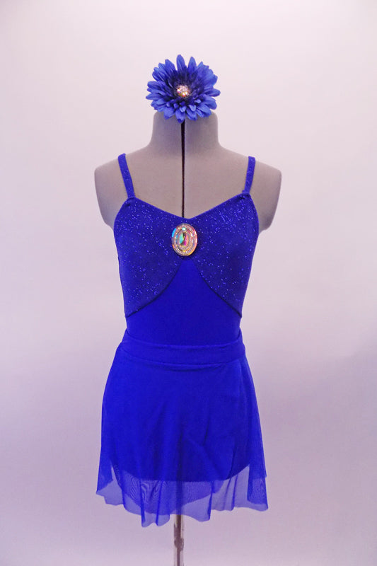 Royal blue leotard has a glittery bust the is accented with a large jewelled accent. The leotard is complemented by a matching sheer short sarong-type skirt. Comes with a jewelled blue floral accessory. Front