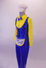 3-piece costume has a bright yellow button front collared shirt with attached blue bow tie. A blue pinstripe black polka dot vest that gathers at the back sits over the shirt & compliments the blue stretch fabric trousers with an attached white mini apron. Comes with white plush chef hat accessory with elastic. Left side