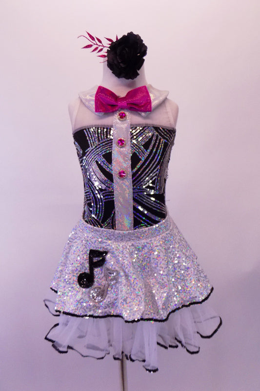 Music-themed leotard with black and silver swirled torso with white shoulders, collar & sheer back. There is a shiny vertical white stripe down the center of the torso with hot pink jewelled buttons that match the bow tie. The silver sequined skirt with white petticoat has black edge & musical note appliques. Front