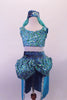Turquoise 2-piece Arabian themed costumes has a fully sequined low-back, tank style half-top. The bottom is a brief with sequined bubble pouffe full bustle with long open front, knee length, turquoise taffeta skirt. The edge of the skirt is trimmed with silver lace that matches the silver & blue waistband & genie hat. Front