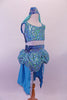 Turquoise 2-piece Arabian themed costumes has a fully sequined low-back, tank style half-top. The bottom is a brief with sequined bubble pouffe full bustle with long open front, knee length, turquoise taffeta skirt. The edge of the skirt is trimmed with silver lace that matches the silver & blue waistband & genie hat. Side