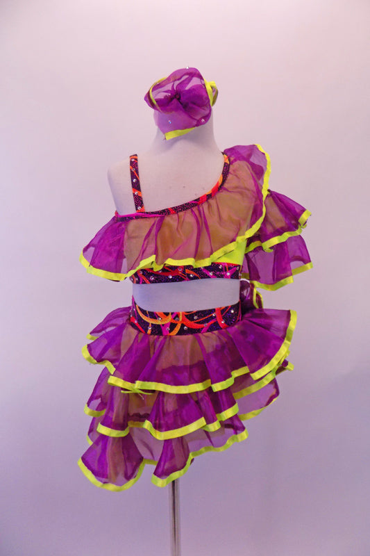 Purple organza ruffles with yellow trim create the uniqueness of this two-piece costume. The layered angled ruffles adorn the yellow, one-shouldered half-top and briefs with red-black-purple swirled banding lined with crystals. Comes with ruffled armband and hair accessory. Front