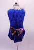 Three-piece costume has a gold half top and briefs which sit below a blue velvet brocade tunic. The tunic is a V-neck with white lace ruffle at the neckline and hip and floral bow accent at back. Comes with lace ruffled velvet gauntlets. Back