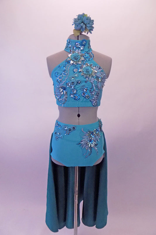 Two-piece turquoise costume is a halter neck half top with a lace-up corset back. The top is covered extensively with beautiful large 3-D floral appliques. The brief bottom has a wide waistband with floral appliques and an attached open front long teal skirt. Comes with a teal floral hair accessory. Front