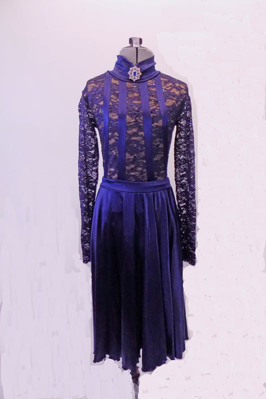 Two-piece navy blue costume has a fully lined lace leotard with open back, long sleeves and four vertical satin stripes in the front. The high neck has a crystal brooch accent. The matching knee-length sateen skirt completes the look. Comes with matching hair accessory. Front