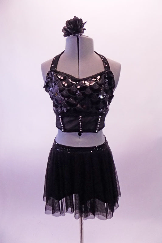 Two-piece black costume has a scale design front sequined haft top with halter neck, crystal accented under-bust band and crystal covered sheer back. The matching short sheer mesh skirt has sequined waistband and attached brief. Comes with a floral hair accessory. Front
