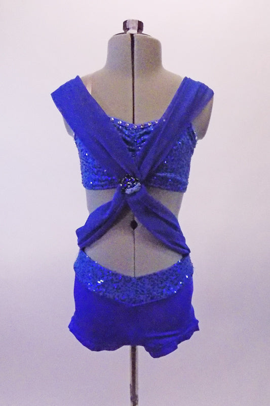 Royal blue costume is a sequined & crystal lines bra top and booty shorts. Two wide chiffon kerchief like bands originate from the back straps and cross over at the front. A large jewelled brooch attached the bands together at the base of the bra front, from where they extend out & are attached at the hips. Front