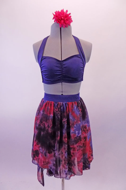Three-piece costume has a navy-blue halter bra top with pinched front and matching briefs. The chiffon high-low skirt has a marbled pattern of blue, black and crimson to create the pop of colour. Comes with a crimson floral hair accessory. Front