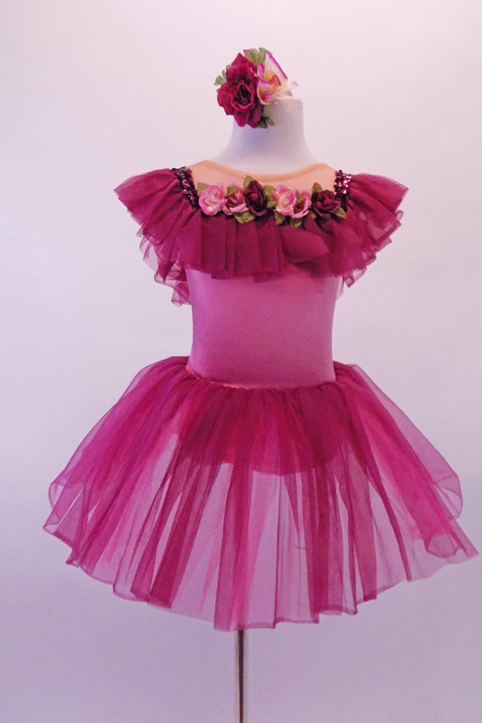 Pink and burgundy ballet dress has a wide burgundy ruffle collar circling from front to back along the nude bust. A sequined trim lines the ruffle and there is a band of roses along the front. The pink torso has an attached burgundy sheer skirt. Comes with matching floral hair accessory. Front