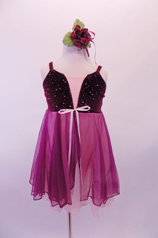 Sweet pink and burgundy dress has a burgundy velvet bust with scattered sequins and pale pink bust.  The pink and burgundy chiffon skirt extends from below the bust. Comes with a burgundy floral hair accessory. Front