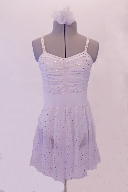 White dress has scattered glitter sequins throughout the fabric. The bodice is ruched to add softness and depth. Crystals line the entire banding of the bustline and straps. Comes with a hair accessory. Front