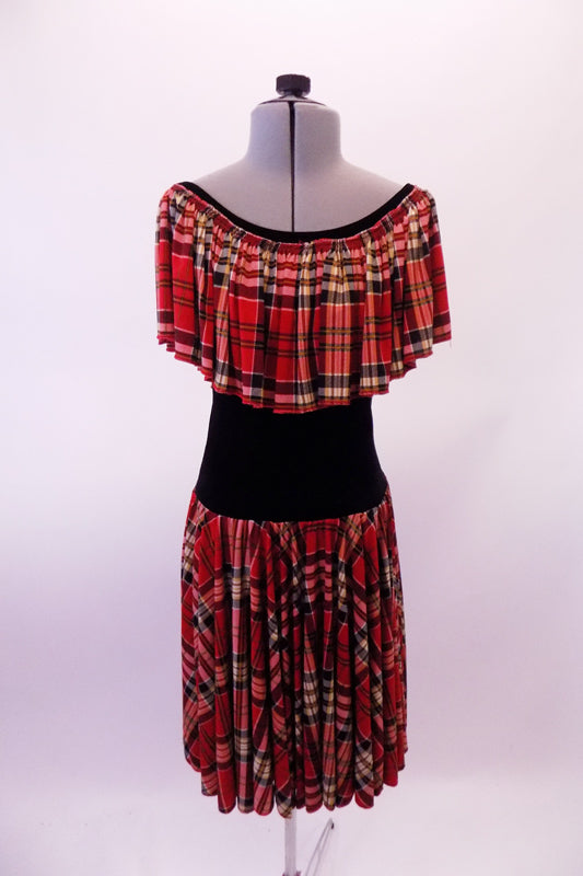 Red based tartan knee-length dress has black lycra torso and a wide ruffle that circles entire shoulder and collar. Comes with a floral hair accessory. Front