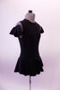 Black leotard dress has a short flowy peplum skirt that attaches in a low front/back princess cut waistline. The back is an open keyhole. Comes with ruffled armband accessory. Side