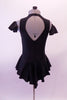 Black leotard dress has a short flowy peplum skirt that attaches in a low front/back princess cut waistline. The back is an open keyhole. Comes with ruffled armband accessory. Back