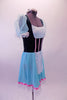 Ballet costume has teal velvet bodice with white lace bust and apron. The sheer aqua pouffe sleeves complement the aqua skirt. Pink ribbon detail accents the bodice and skirt edge. Wide white lace trim edges the skirt and sleeves. Comes with a white floral wreath accessory. Side