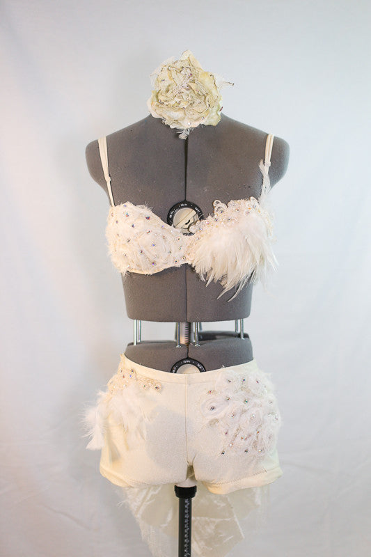 Custom designed, ivory bra, and shorts with intricate appliqué, beading, feathers, and  crystals. Back has tail of layered tulle, crystals and rose fabric, front