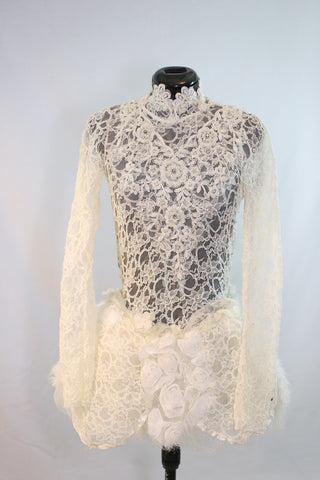 Custom, ivory lace long sleeved dress has open back lined with thick beaded bridal appliqué. Skirt is layers of tulle and silk rose fabric. covered crystals. Front