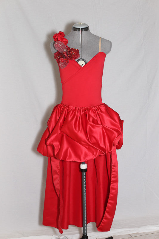 Red heavy sateen stretch fabric full dress. Skirt is open front, with large ruched bustle. Right shoulder is ruffled with a large flower crystal appliqué,  front