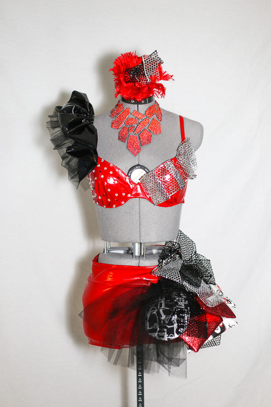 Red pleather 2 piece jazz costume with ruffle along the right shoulder. Shorts have a pouf-like attachment with foil,tulle and padded, decorative fabric pieces, front