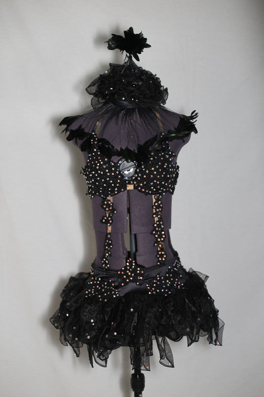 Black bra attached to skirt by lace appliqués. The bra is extensively covered with  large AB Swarovski. Has an attached panty. Front
