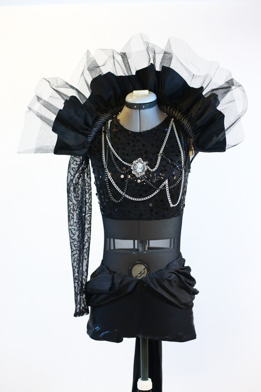 Black sequined bodice with single sleeve, adorned with silver and black chains and a large cameo. Leathery shorts with sash and removable large tulle collar, front