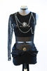 Black sequined bodice with single sleeve, adorned with silver and black chains and a large cameo. Leathery shorts with sash, front