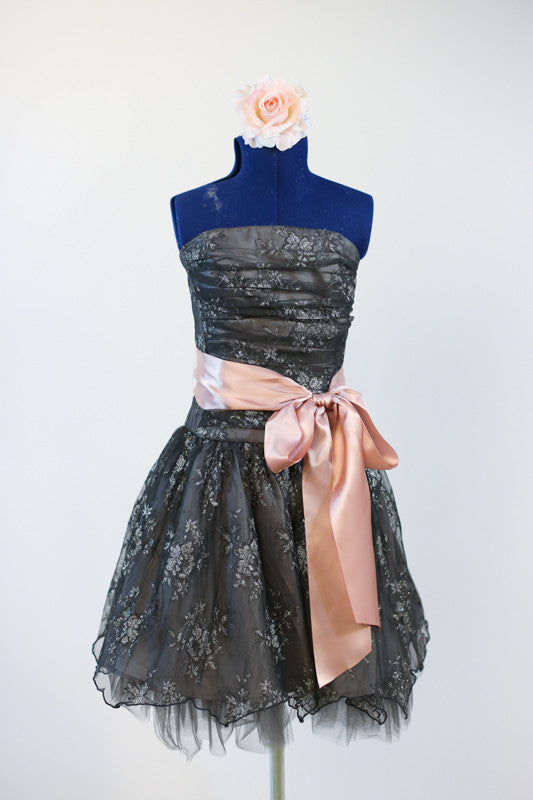 Dark grey dress with pewter lace overlay, has large pink sash and flower headpiece front