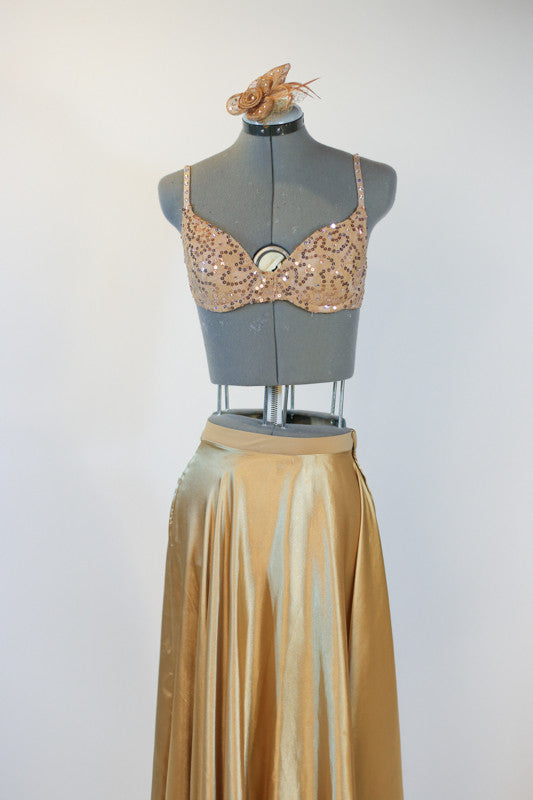 Gold shiny spandex brief, gold sequined bra and long flowing, ankle length, gold wrap skirt.skirt. with a gold hairpiece, front