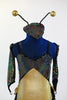 Black hologram spandex leotard has layers of gold and black ruffles. Comes with antennae hat and gantlets, front