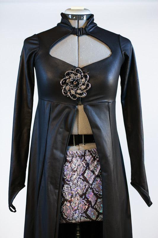 Long black leather-like coat  with large Swarovski broach accent. The coat is open in the front to reveal the snake-skin shorts. Zoom front