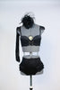 Black bustier style bra with fringed epaulets and gold chain details. at front. Has ruffled, high-waisted panty, long black gloves and a black head piece. Front