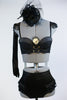 Black bustier style bra with fringed epaulets and gold chain details. at front. Has ruffled, high-waisted panty, long black gloves and a black head piece. Front zoom