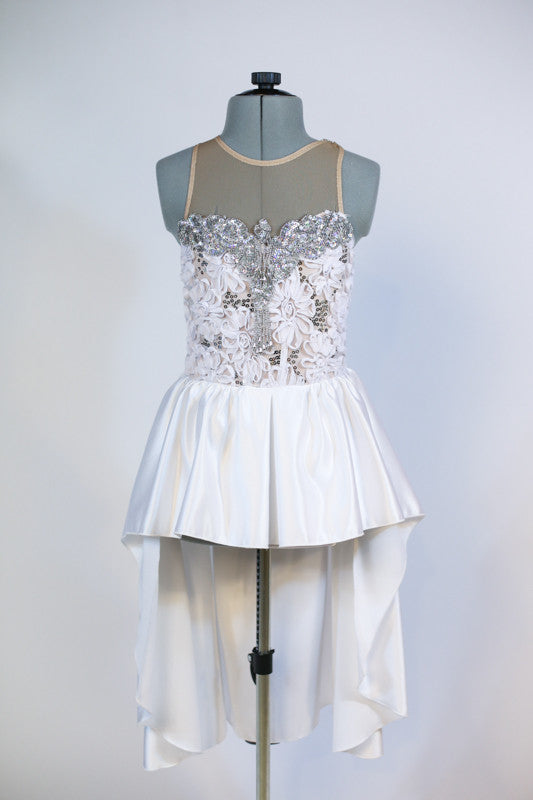 White rose fabric bodice is heavily embossed with large silver appliqués and crystals attached to white high-low skirt with pewter grey long bow at back, Front