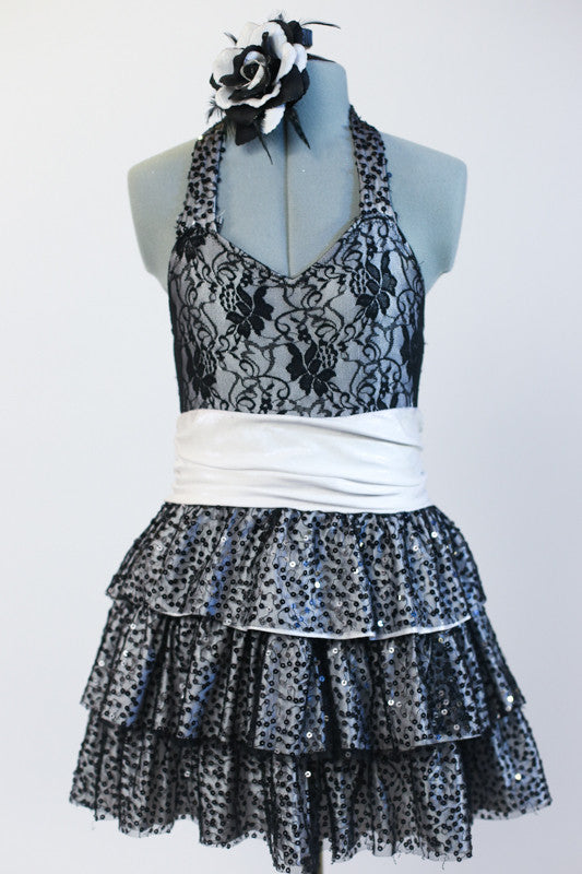 Black halter lace dress with attached panty has wide white stretch waistband and layered sequined skirt. Comes with matching black and white rose hair accessory. Front Zoom