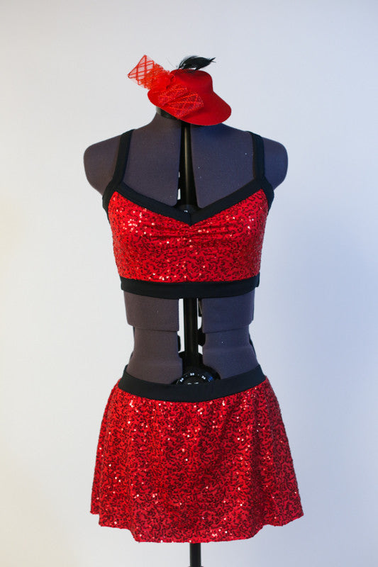 Red sequined bra top has black edging, criss-cross straps and a matching skirt with attacked black shorts. Comes with mini red jazz hat accessory. Front