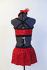 Red sequined bra top has black edging, criss-cross straps and a matching skirt with attacked black shorts. Comes with mini red jazz hat accessory. Back