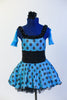 Blue glitter dress has black polk-a-dots & black gathered waistband. Dress has layered black petticoat skirt, blue gauntlets & black flower hair accessory. Front