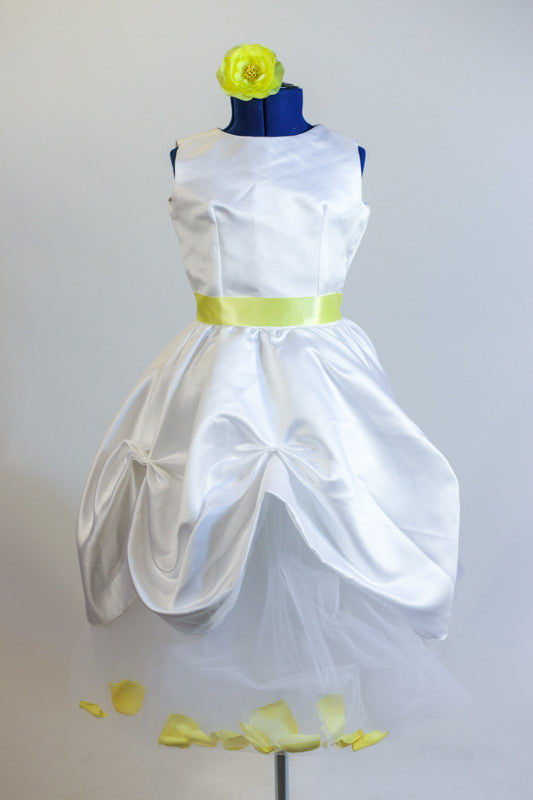 Long white tulle skirt contains yellow rose petals. Tulle shirt sits below white sateen ruched dress with soft yellow satin sash and yellow floral hair piece. Front
