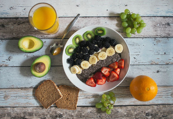 A bowl of healthy, sweet snack fruit surrounded by fruits and vegetables