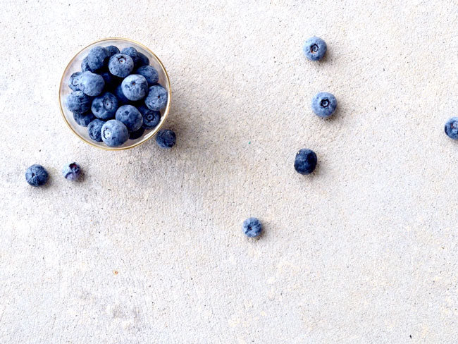 A small bowl of blueberries on a white surface