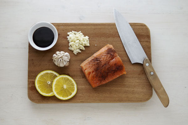 A piece of salmon and some garlic on a wooden cutting board