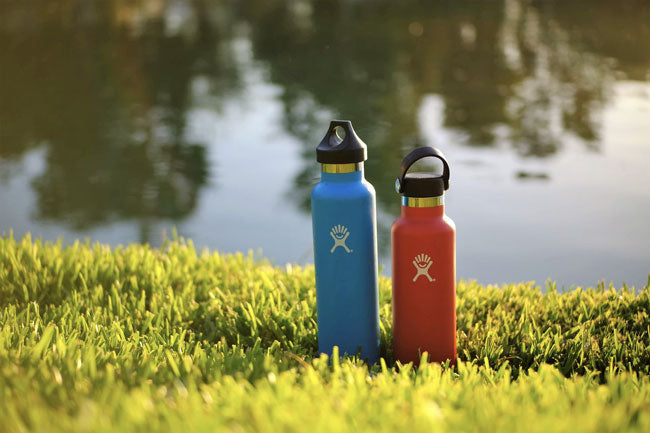 Two multicolored water bottles posed on the grass