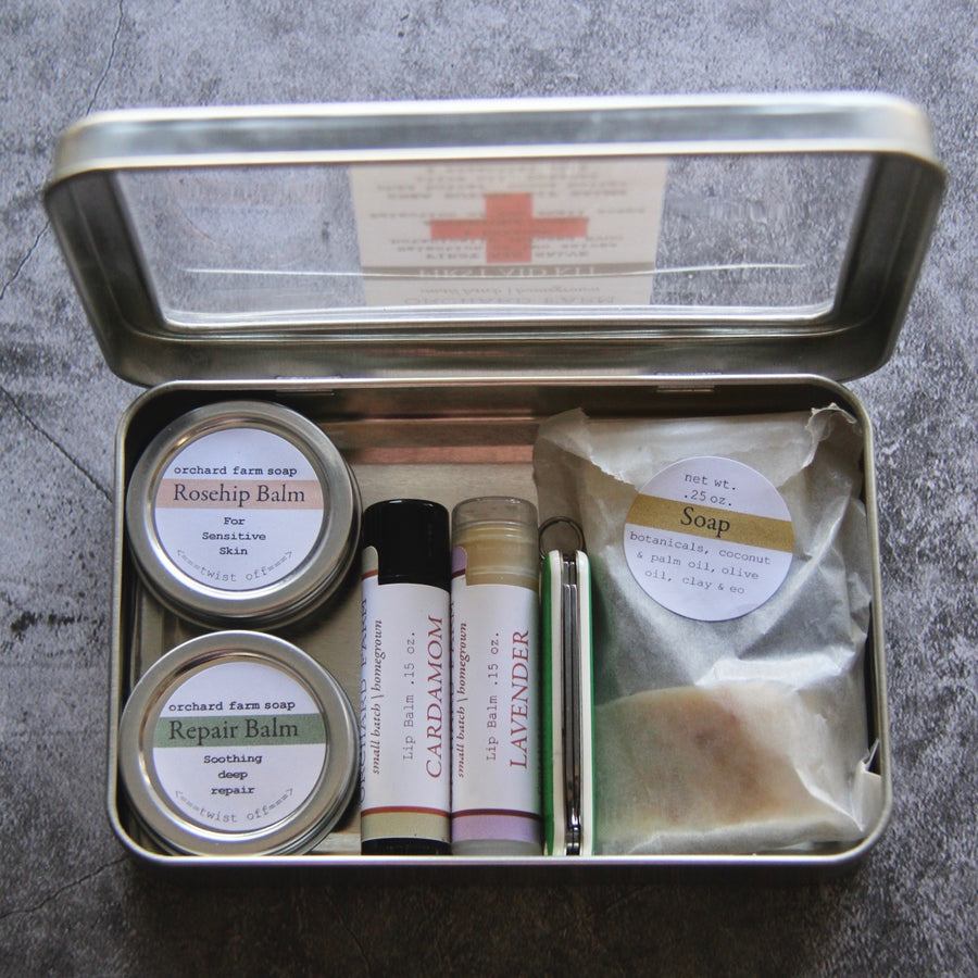 First Aid kit includes 2 small tins of salve, 2 lips balms, 3 small soaps and bandaids