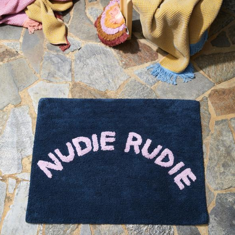 We love the Tula Nudie Bath Mat in Denim by Sage + Clare!  Cheeky 'Nudie Rudie' text adorns this tufted denim bath mat, adding a daily dose of fun to your bathroom.